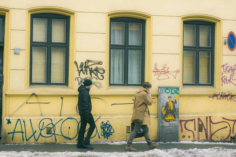 two goys passing a wall that has tags and graffiti on it - oslo