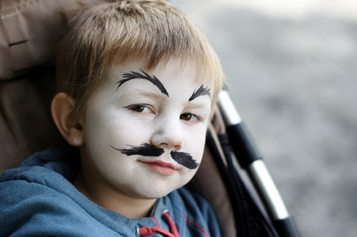 a boy with painted mustache