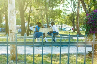 A couple in school uniforms sitting on a bench in Haiti - Petion-Ville
