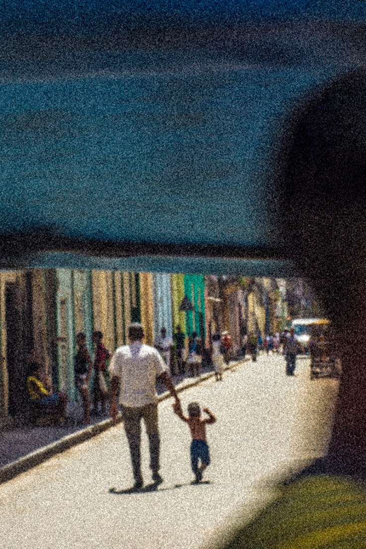 father and child walking on a cuban street
